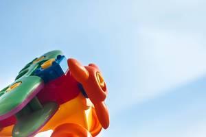 Nahaufnahme buntes Spielzeug-Flugzeug aus Kunststoff vor blauem Himmel