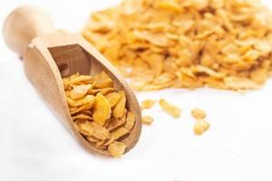 Nahaufnahme Cornflakes in hölzerner Schaufel vor Haufen mit Cornflakes mit Schärfentiefe