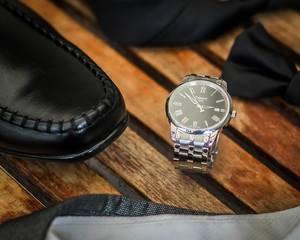 Nahaufnahme der Accessoires des Bräutigams wie luxuriöse Uhr und elegante Lederschuhe auf Holz