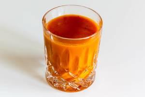 """Nahaufnahme der spanischen Gemüsesuppe """"Gazpacho"""" von Innocent in einem Glas, isoliert vor weißem Hintergrund"""