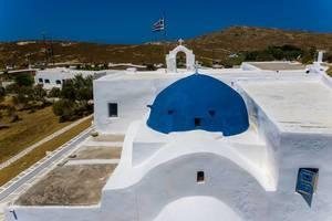 Nahaufnahme des blauen Kuppeldachs des Klosters von Agios Ioannis Detis, mit wehender Griechenlandfahne im Hintergrund