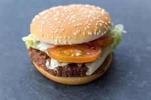 """Nahaufnahme des fleischlosen Burger """"Big Vegan TS"""" von McDonalds auf dunklem Untergrund mit Sojabratling, Weizeneiweiß, Blattsalat und Sesam"""