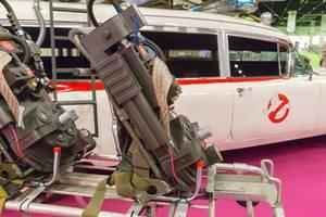 Nahaufnahme des Ghostbusters Proton Pack und Auto Ecto-1 im Hintergrund