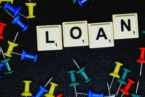 """Nahaufnahme des Texts """"Loan"""" - Darlehen mit Reißzwecken"""