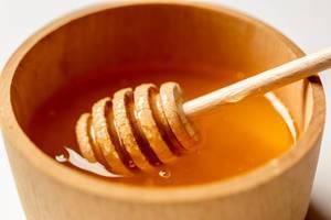 Nahaufnahme - Ein Honigstab wird in Honig getaucht