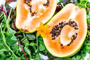 Nahaufnahme einer aufgeschnittenen Papaya Frucht mit Kernen, auf grünem Salat, mit einer Narzisse dekoriert