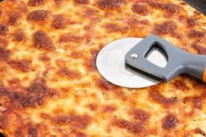 Nahaufnahme einer fertigen Pizza Margherita mit viel Käse und rundem Pizzamesser