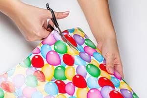 Nahaufnahme einer Frau beim Geschenkpapier schneiden mit einer Schere