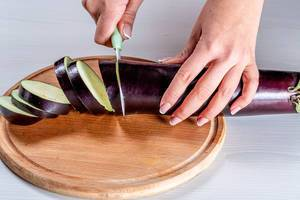 Nahaufnahme einer Frauenhand mit Messer, beim schneiden einer Aubergine