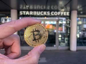 Nahaufnahme einer goldenen-Bitcoin-Münze vor Starbucks Coffee House am Friesenplatz in der Kölner Altstadt-Nord