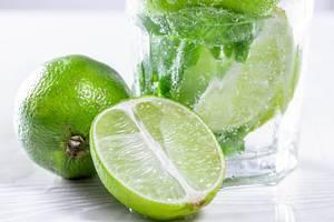 Nahaufnahme einer halbierten Limette vor einem gekühlten Mojitococktail