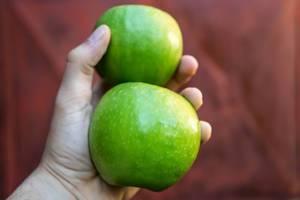 Nahaufnahme einer Hand eines Mannes der zwei Äpfel hält
