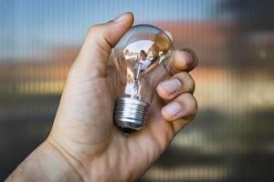 Nahaufnahme einer Hand mit klarer Glühbirne