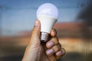 Nahaufnahme einer Hand mit matter LED Glühlampe