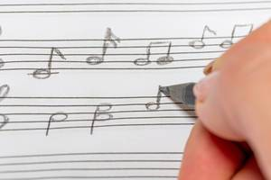 Nahaufnahme einer Hand mit schwarzem Bleistift die Noten zeichnet