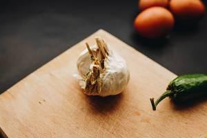 Nahaufnahme einer Knoblauchknolle auf einem Schneidebrett. Eier und Chilischote im Hintergrund