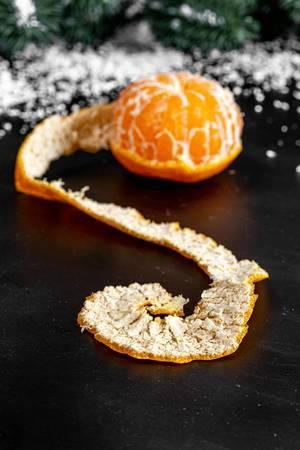 Nahaufnahme einer Mandarine mit runder geschälter Schale auf dunkler Oberfläche