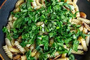 Nahaufnahme einer Nudelpfanne mit Spinat, Champignons, Lauchzwiebeln und Spirelli-Nudeln