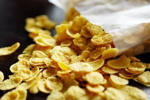 Nahaufnahme einer offenen Packung Cornflakes mit teilweise herausgefallenem Inhalt