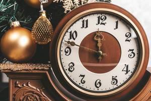 Nahaufnahme einer Spannungsuhr als Symbol der Neujahrswende neben einem dekorierten Tannenzweig