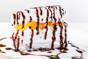 Nahaufnahme einer Stück Kuchen mit Orangenscheiben, Sahne und zerlaufener Schokoladensauce