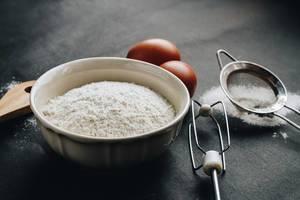 Nahaufnahme einer typischen Backszene: Mehl und weitere Zutaten