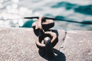 Nahaufnahme einer verrosteten Kette, Meer im Hintergrund