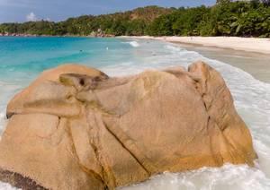 Nahaufnahme eines braunen Granitfelsen am Strand Anse Lazio auf Praslin, Seychellen, mit badenden Touristen im Hintergrund