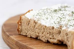 Nahaufnahme eines Brots, bestrichen mit Sauerrahm und feinen Kräutern