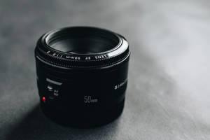 Nahaufnahme eines Canon Objektivs vor dunklem Hintergrund