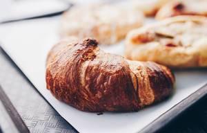 Nahaufnahme eines Croissants mit Butter. Schnelles Frühstück