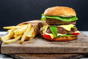 Nahaufnahme eines doppelten Hamburgers / Cheeseburger mit Pommes Frites, auf alten Küchenbrettern mit schwarzem Hintergrund