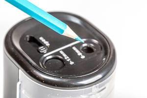 Nahaufnahme eines elektrischen Anspitzer und blauem Buntstift