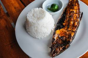 Nahaufnahme eines gegrillten Milchfisch mit Reis, auf einem Holztisch