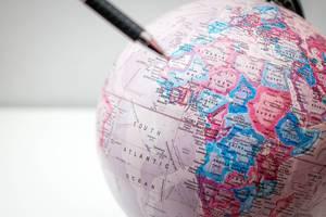 Nahaufnahme eines Globus mit Stift im Vordergrund