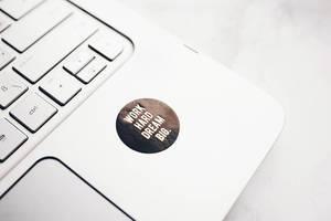 Nahaufnahme eines motivierenden Aufkleber auf einem Laptop - WORK HARD, DREAM BIG