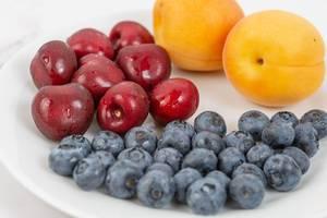 Nahaufnahme eines Obsttellers mit Heidelbeeren, ganzen Aprikosen und gewaschenen Kirschen