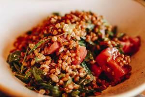 Nahaufnahme eines Salats mit Avocado, Tomate und Rukola