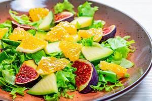 Nahaufnahme eines Salats mit Feigen, Orangen-Stücken und Mango auf einem Teller