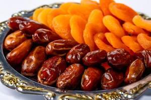 Nahaufnahme eines Silbertabletts mit getrockneten Datteln und Aprikosen-Trockenobst
