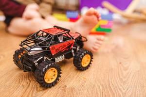 Nahaufnahme eines Spielzeugautos mit Kind im Hintergrund