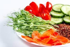 Nahaufnahme eines vegetarischen Mittagessens mit frischem Gemüse, Erbsensprossen und eingelegtem, roten Ingwer