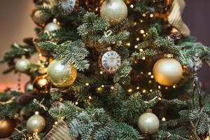 Nahaufnahme eines Weihnachtsbaumes beschmückt mit Weihnachtskugeln und einer goldenen Uhr