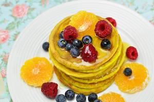 Nahaufnahme gestapelte Pfannkuchen mit Ahornsirup, Beeren und Orangenscheiben