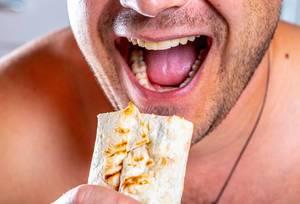 Nahaufnahme hungriger Mann mit geöffnetem Mund und frisch gebratenem Shawarma in der Hand