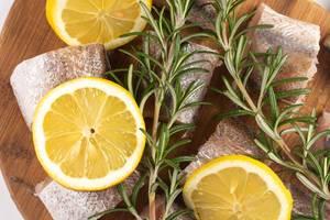Nahaufnahme in Stücke geschnittener Hecht mit Zitronenscheiben und Rosmarin auf hölzernem Küchenbrett