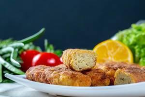 Nahaufnahme kalorienarme Fischstäbchen vor Zitronen und Tomaten auf weißem Teller