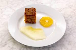 Nahaufnahme - Karottenkuchen auf weißem Teller mit einer Scheibe Orange und Honigmelone