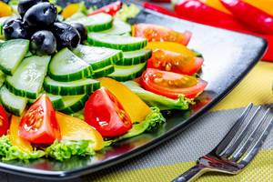 Nahaufnahme nahrhafter Salat mit Gurke, Tomate, Paprika und Oliven auf schwarzem Teller