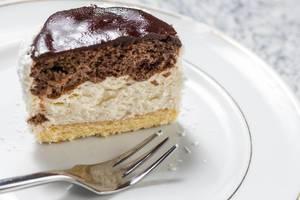 Nahaufnahme schmackhafter Nachtisch mit Schokoladenglasur mit Gabel auf weißem Teller